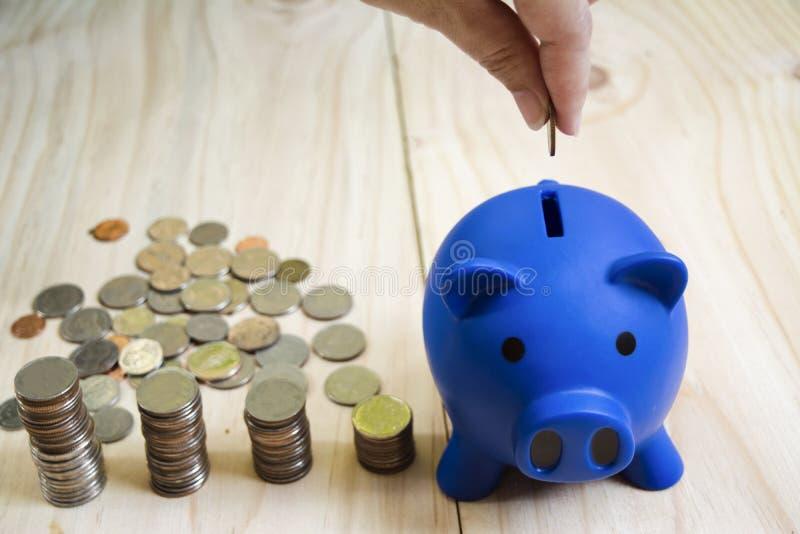妇女手下落硬币蓝色存钱罐和硬币堆在木地板被安置,与保存和投资的概念财政的 图库摄影