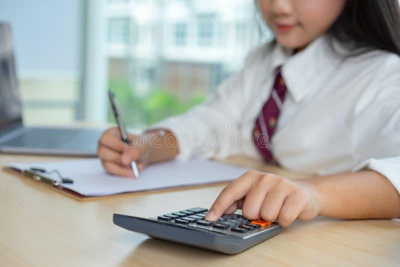 妇女手与计算器一起使用 免版税库存图片