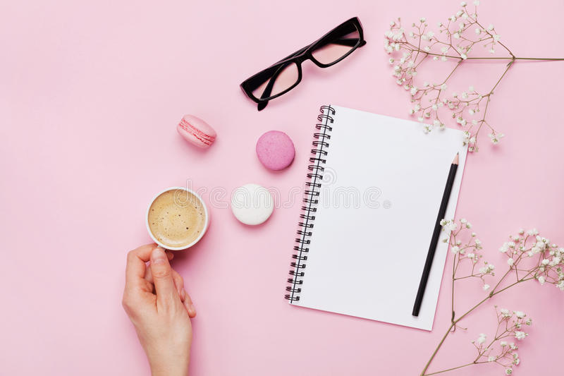 妇女手举行咖啡、蛋糕macaron、干净的笔记本、镜片和花在桃红色桌上从上面 女性运转的书桌 免版税库存图片