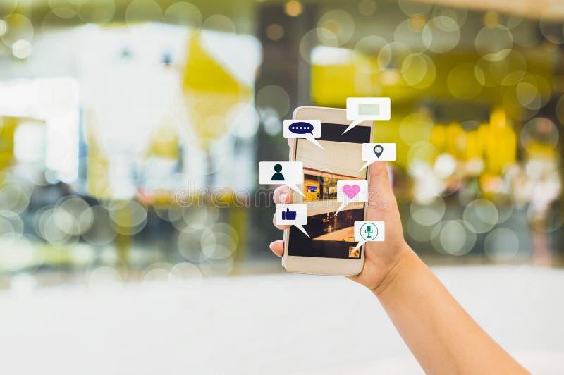 妇女手举行智能手机份额社会媒介,与被弄脏的背景百货店和bokeh,概念生活方式和 免版税库存照片