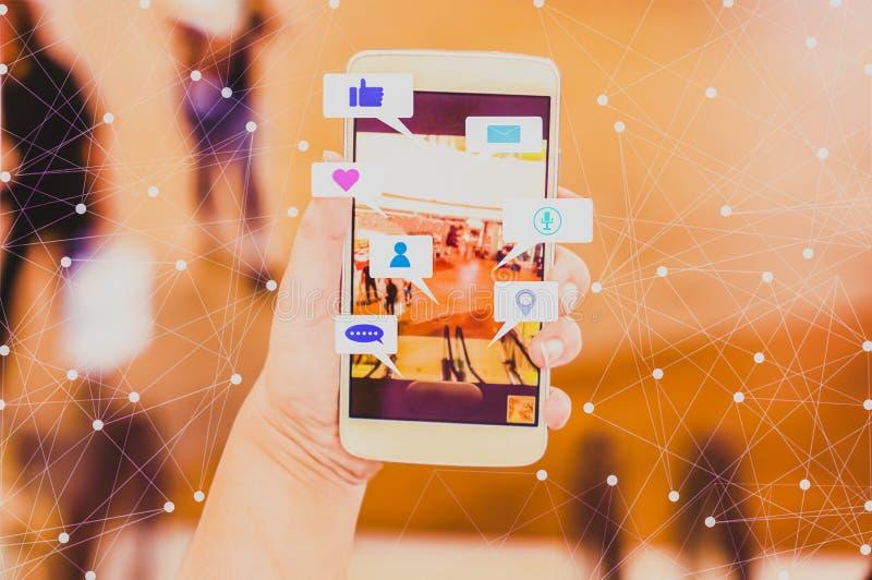 妇女手举行智能手机份额社会媒介,与被弄脏的背景百货店和bokeh,概念生活方式和 免版税库存图片