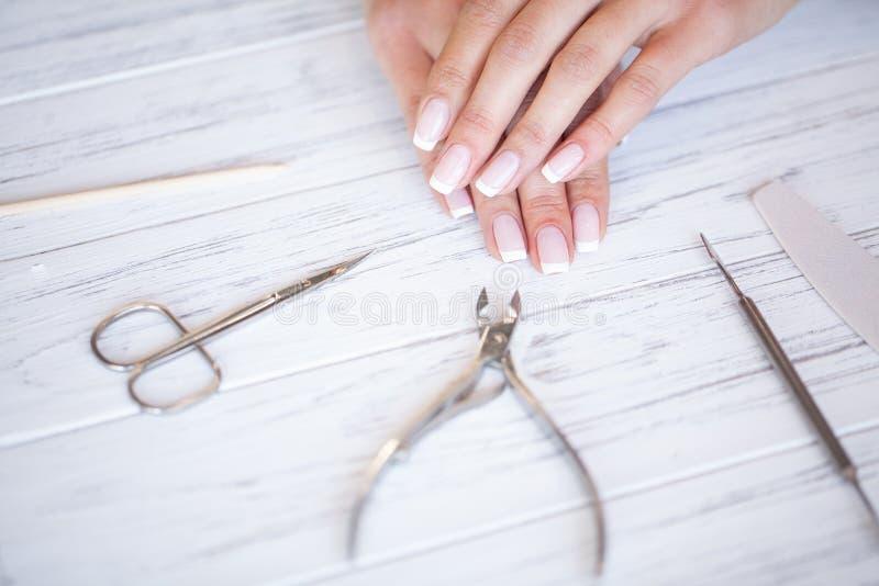 妇女手关心 美好的女性手特写镜头有温泉修指甲在发廊 美容师归档的客户 免版税库存照片