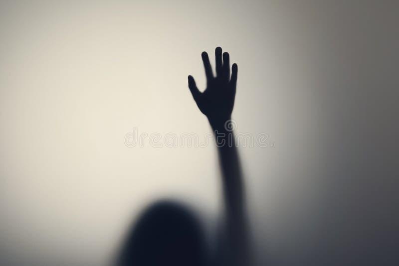 妇女手剪影在玻璃门后的 消沉,恐惧,惊恐发作的概念 库存图片