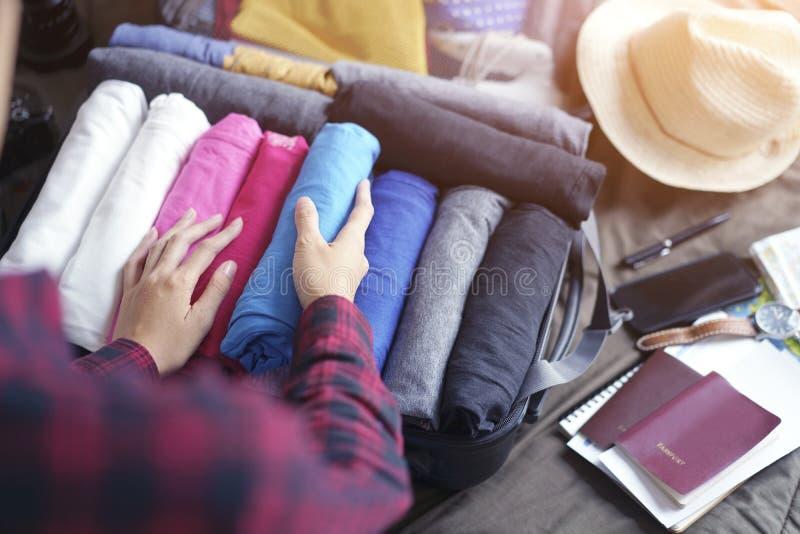 妇女手包装在手提箱袋子的衣裳在床上,为新的旅途和旅行做准备对长的周末 免版税库存图片