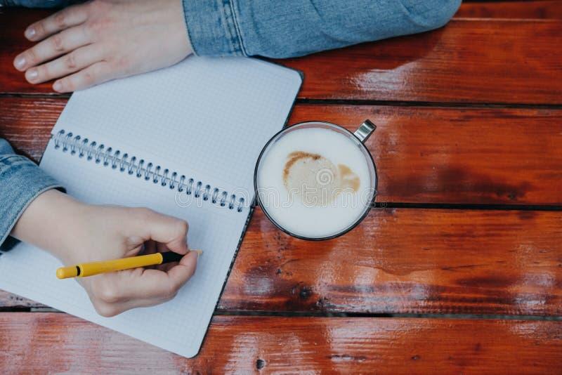 妇女手在小笔记本的文字学报,当喝coff时 免版税库存照片