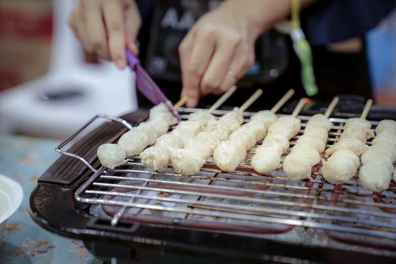 妇女手幻灯片在烤的机器被烤的肉丸 库存图片