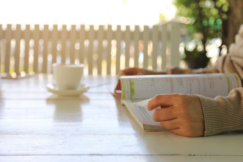妇女手开头杂志和读书在木桌上在家 免版税库存照片