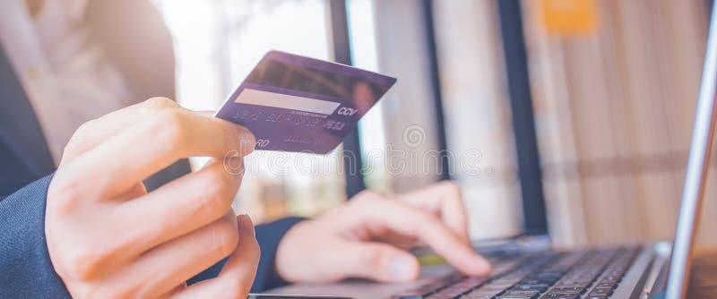 妇女手拿着一张蓝色信用卡 并且使用一手提电脑 e 免版税图库摄影
