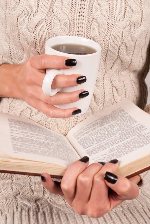 妇女手拿着纸书,她在毛线衣 免版税库存照片