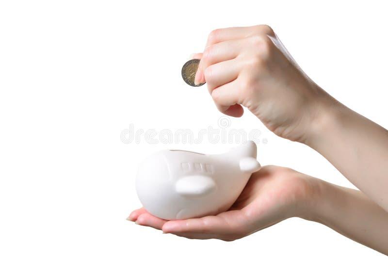妇女手放置在一架存钱罐飞机的一枚硬币 免版税库存照片