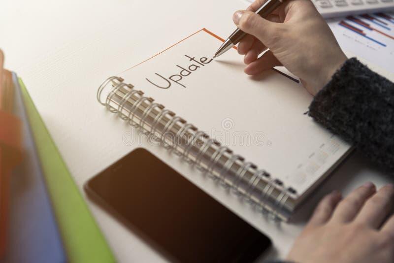 妇女手文字在一个笔记本的词更新在书桌上 项目 库存照片