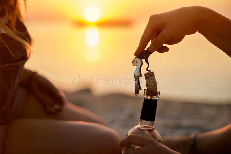 妇女手温文地打开一个瓶与拔塞螺旋的白酒并且去掉黄柏桶盖 女性用途瓶盖启子 库存照片