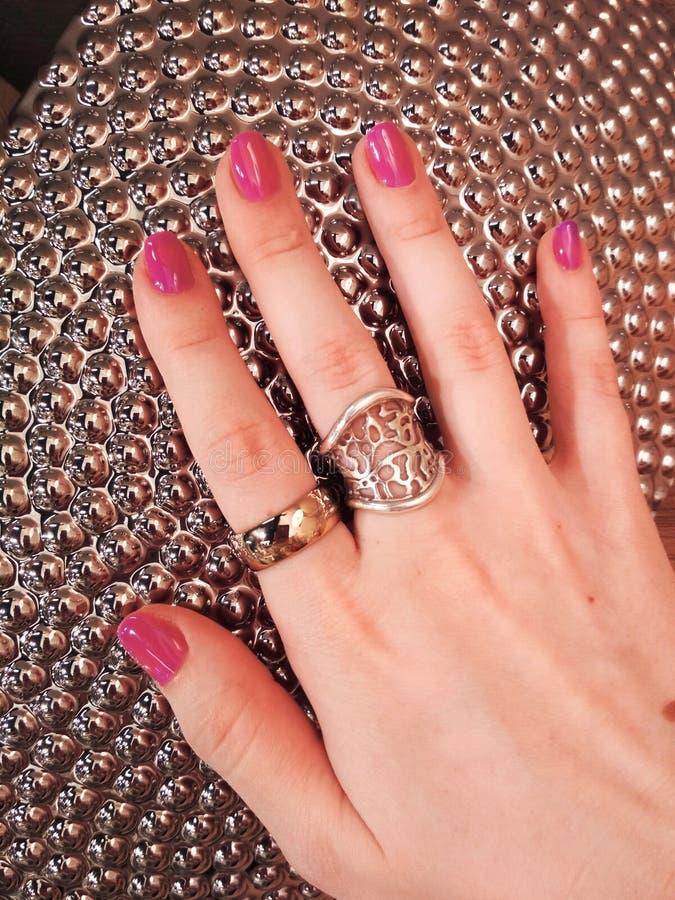 妇女手珊瑚桃红色修指甲胶凝体指甲油样片秀丽时尚银装饰纹理照片 图库摄影