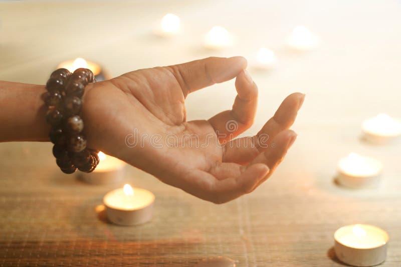妇女手瑜伽和凝思在蜡烛温暖的发光的背景 免版税图库摄影