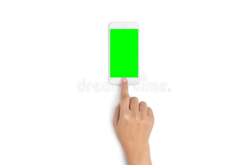 妇女手用途在手机按钮的手指接触有从顶视图的空白的绿色屏幕的,隔绝在白色背景 免版税库存图片