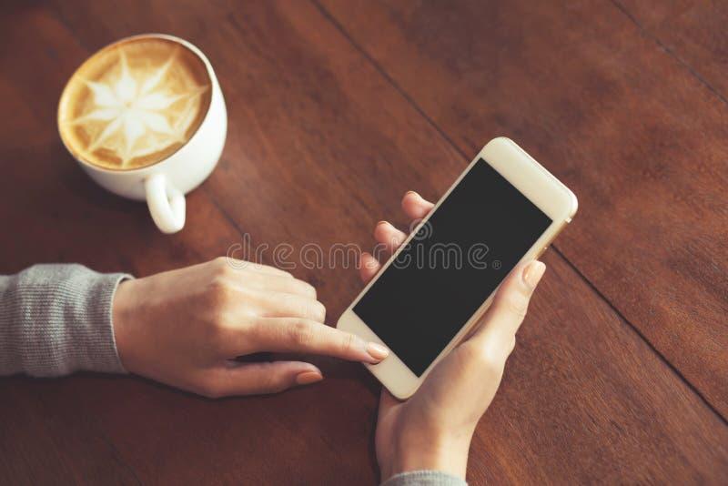 妇女手的关闭对负使用流动智能手机空白拷贝空间屏幕空为您在顶视图的广告的短信 库存照片