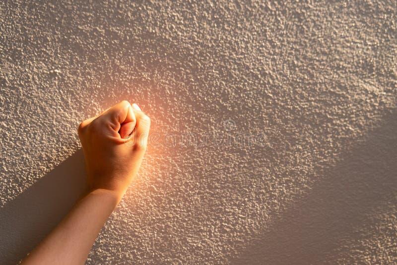妇女手的关闭接触有阳光的一个白色混凝土墙, 库存图片