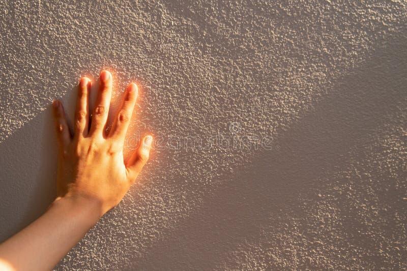妇女手的关闭接触有阳光的一个白色混凝土墙, 免版税库存照片