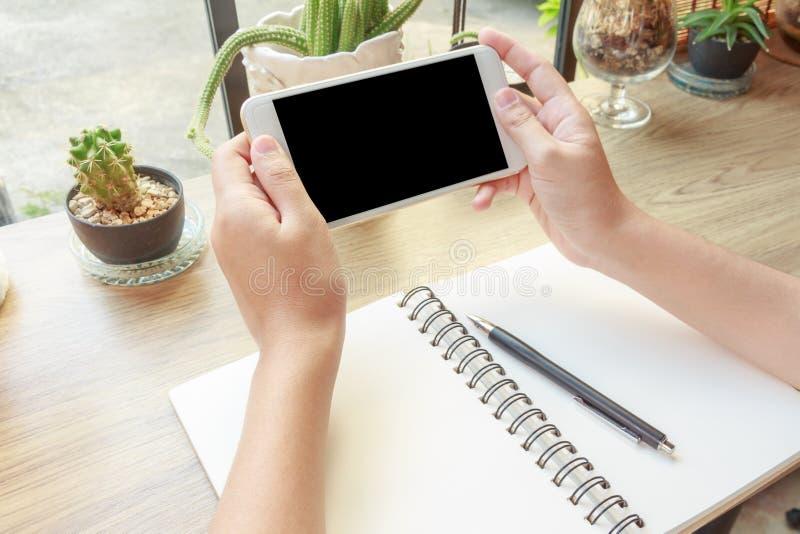 妇女手的特写镜头的概念拿着手机的观看V 库存图片