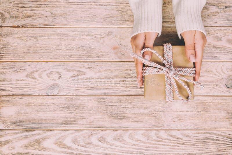 妇女手给被包裹的华伦泰或其他假日手工制造礼物在纸与最高荣誉 当前箱子,礼物的装饰 免版税库存照片