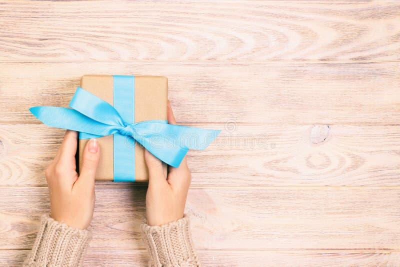 妇女手给被包裹的华伦泰或其他假日手工制造礼物在纸与最高荣誉 当前箱子,礼物的装饰 库存照片
