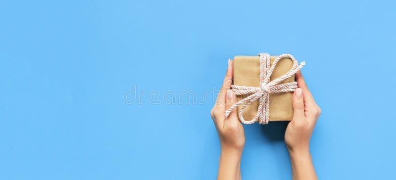 妇女手给被包裹的华伦泰或其他假日手工制造礼物在纸与桃红色丝带 当前箱子,礼物的装饰 免版税图库摄影