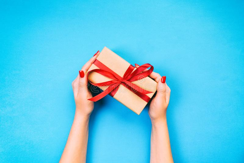 妇女手给被包裹的华伦泰或其他假日手工制造礼物在纸与红色丝带 当前箱子,礼物的装饰 库存图片