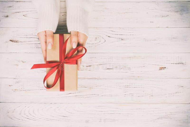 妇女手给被包裹的华伦泰或其他假日手工制造礼物在纸与红色丝带 当前箱子,礼物的装饰 库存照片