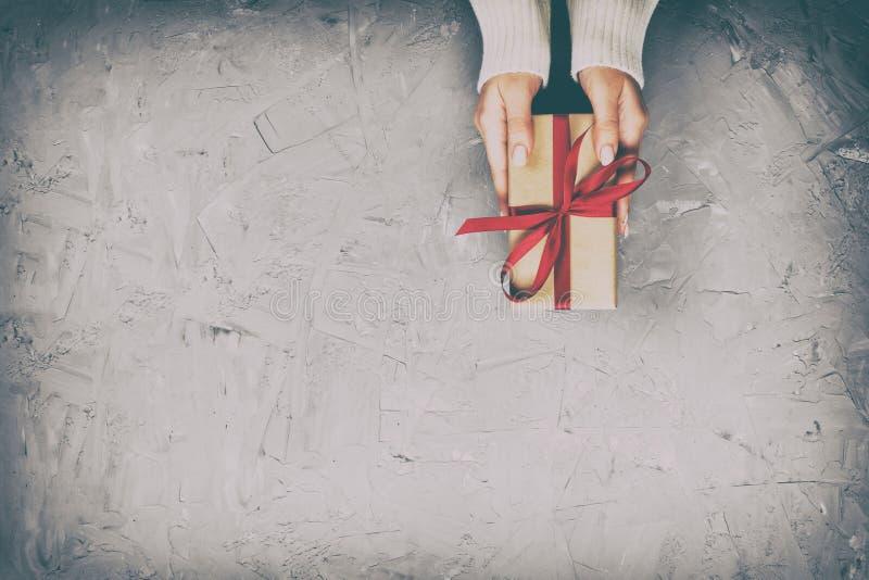 妇女手给被包裹的华伦泰或其他假日手工制造礼物在纸与红色丝带 当前箱子,礼物的装饰 图库摄影