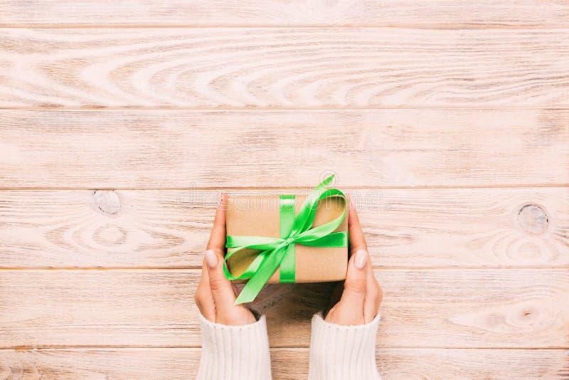 妇女手给被包裹的华伦泰或其他假日手工制造礼物在纸与绿色丝带 当前箱子,礼物的装饰 图库摄影