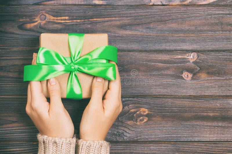 妇女手给被包裹的华伦泰或其他假日手工制造礼物在纸与绿色丝带 当前箱子,礼物的装饰 库存照片
