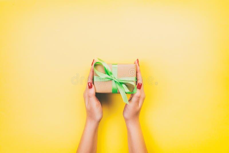妇女手给被包裹的华伦泰或其他假日手工制造礼物在纸与贪婪丝带 当前箱子,礼物的装饰 库存照片