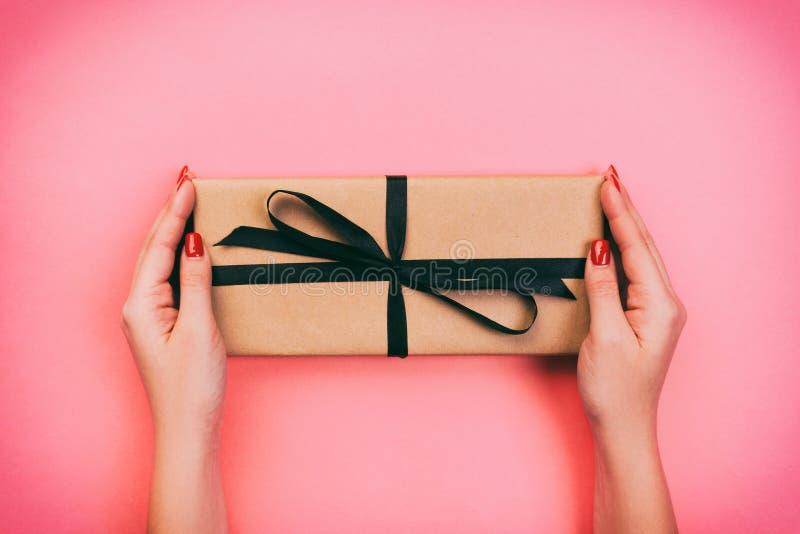 妇女手给被包裹的华伦泰或其他假日手工制造礼物在纸与黑丝带 当前箱子,礼物的装饰 免版税库存照片