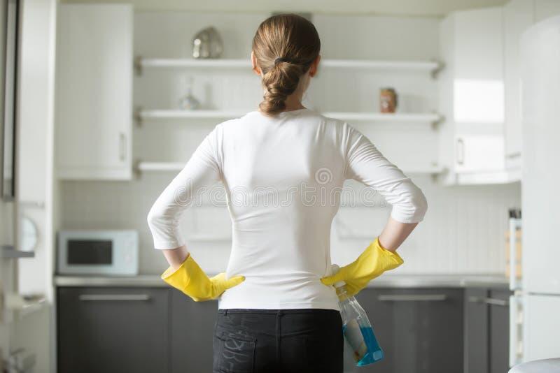 妇女手背面图在她的臀部的,观察厨房 免版税图库摄影