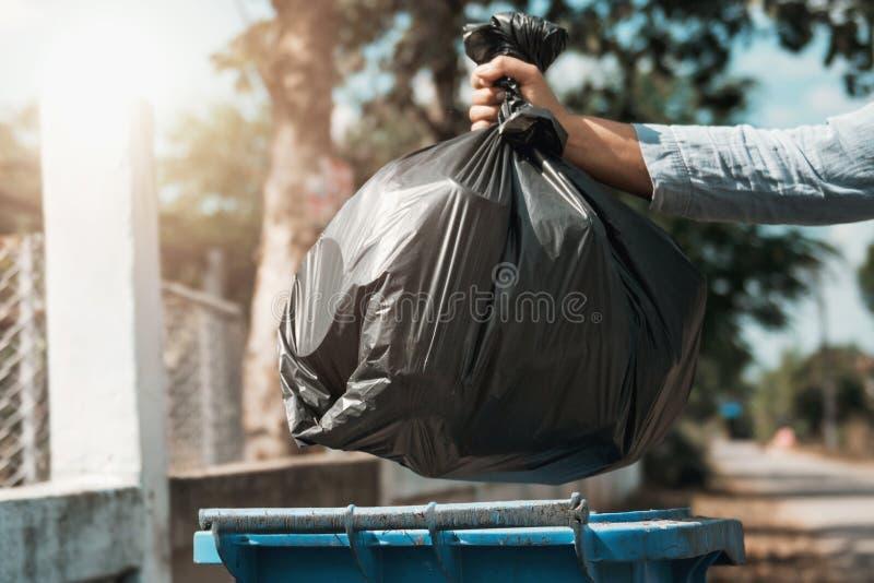 妇女手藏品垃圾袋投入破坏 免版税图库摄影