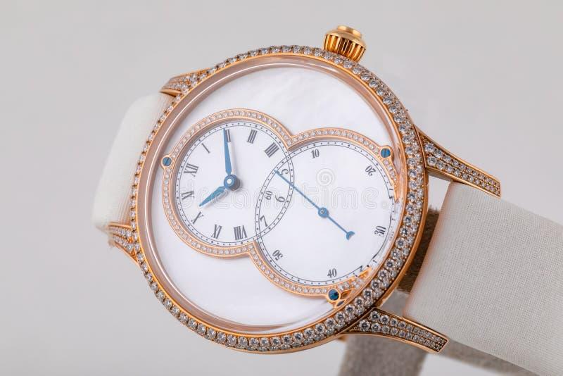 妇女手表,有白色皮带,金刚石的,与白色拨号盘,黑数字和蓝色顺时针,在白色背景隔绝的秒表 库存图片
