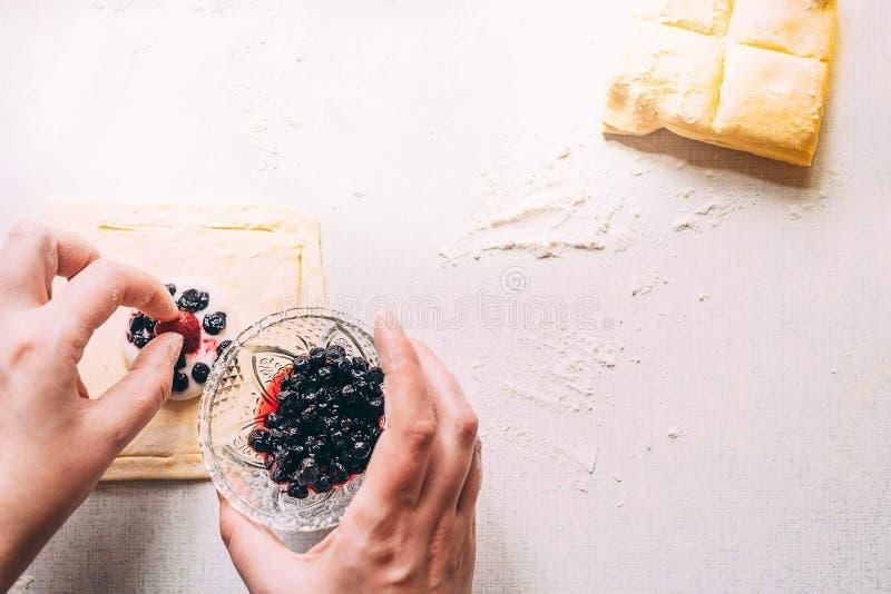妇女手通过放置莓果准备一个蛋糕在面团 在白色桌谎言面团 晴朗的早晨 平的位置 免版税图库摄影