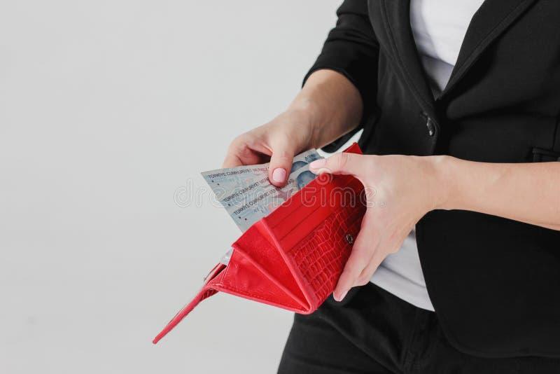 妇女手采取金钱从红色钱包的土耳其里拉在灰色backg 库存图片