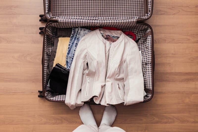 妇女手顶视图包装一次新的旅途的一件行李 库存图片