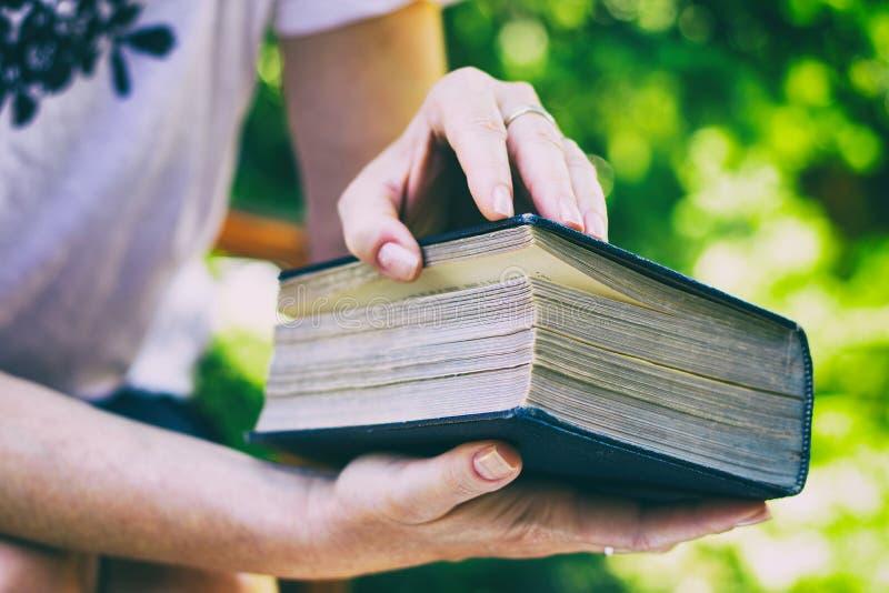 妇女打开一本大旧书 免版税库存图片