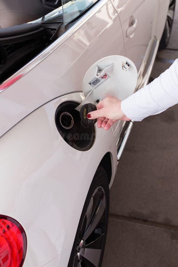妇女打开她的汽油箱盖帽加油 免版税图库摄影