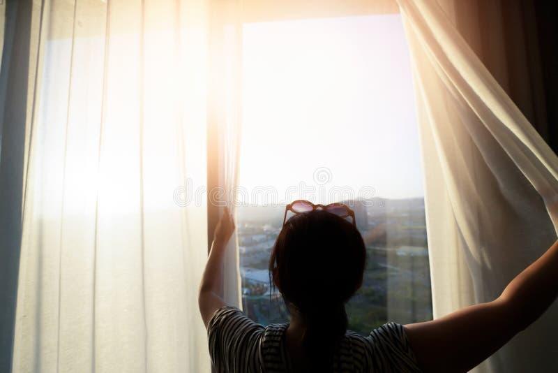 妇女打开帷幕在窗口早晨 免版税库存照片