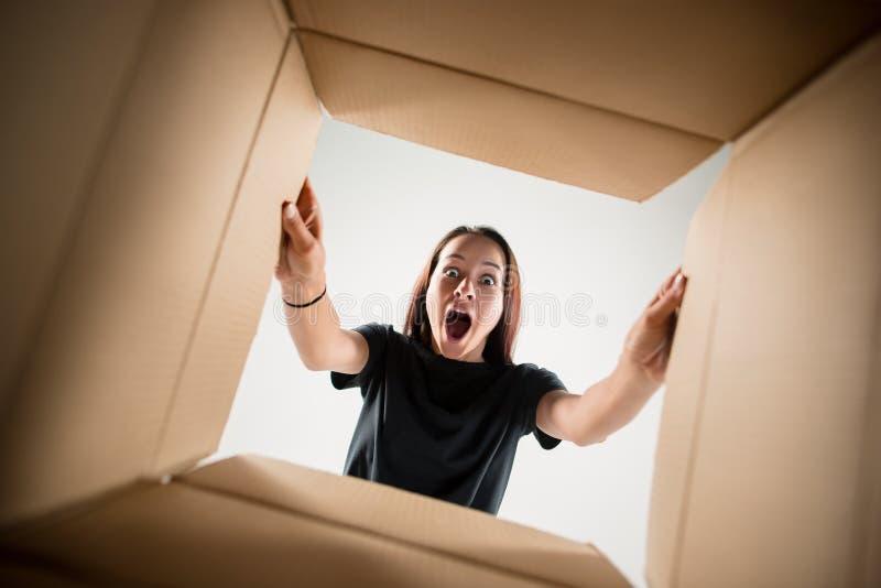 妇女打开的和打开的纸盒箱子和看里面 免版税库存图片