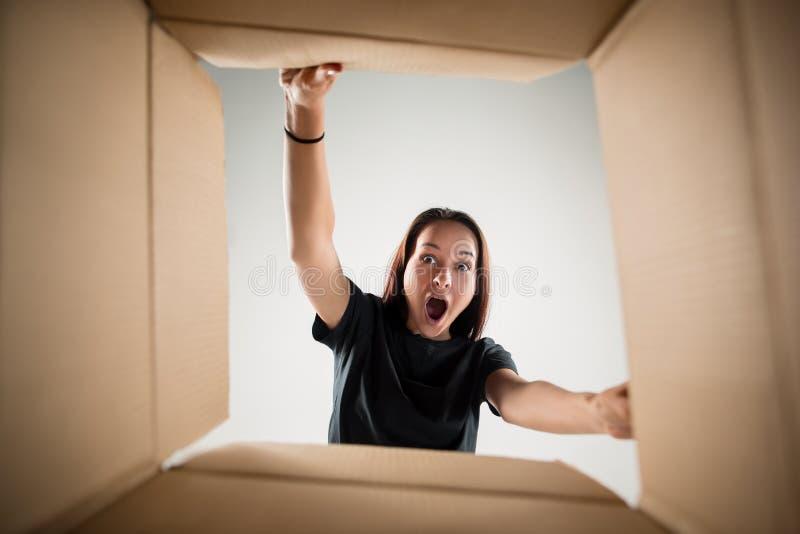 妇女打开的和打开的纸盒箱子和看里面 免版税库存照片