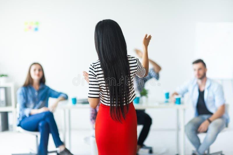 妇女打手势用手的企业教练背面图  免版税库存图片