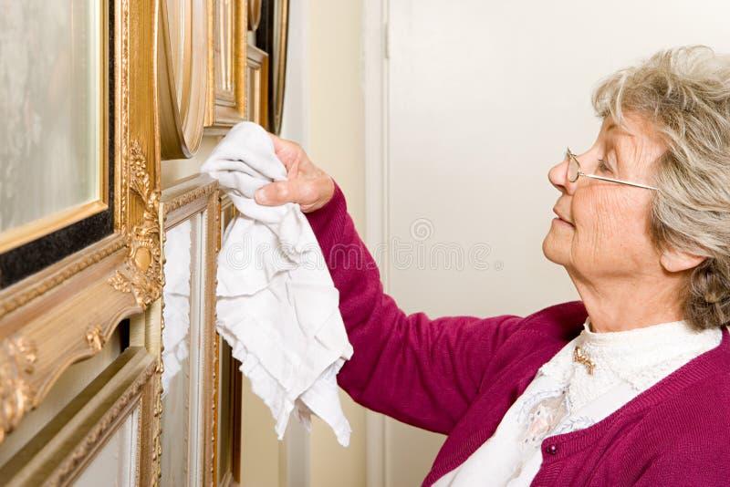 妇女打扫灰尘画框 库存照片