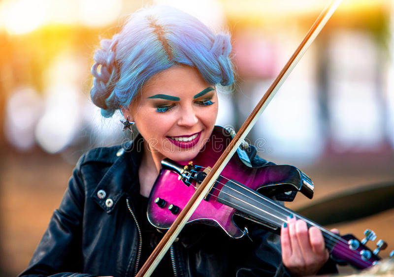 妇女执行在室外小提琴的公园的音乐 执行爵士乐的女孩图片