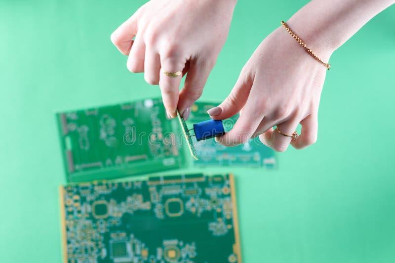 妇女技术员装配在电路板的一台电容器 检查瑕疵电路板的女性技术员 免版税图库摄影