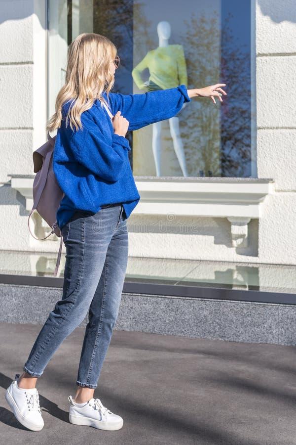 妇女把手指指向商店窗口 免版税库存照片