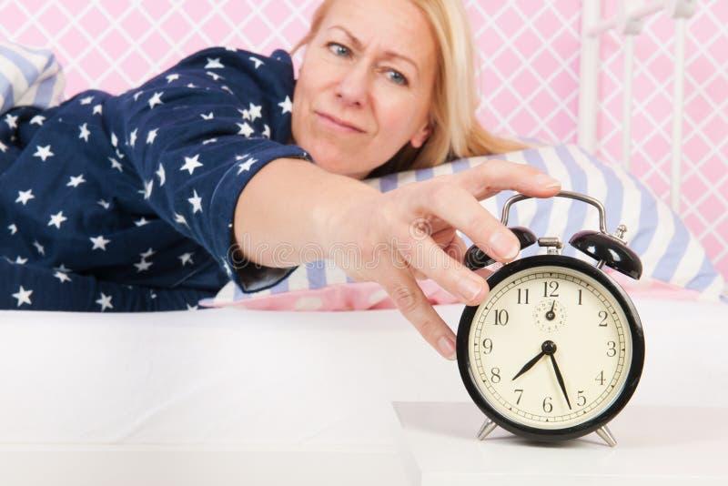 妇女投入了闹钟 免版税库存图片